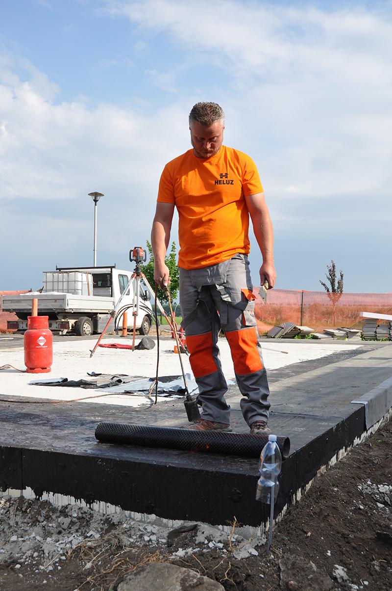 Asfaltovaný pás postupne natavujeme celoplošne plynovým horákom s presahom min. 150 mm za hranu budúcej steny.