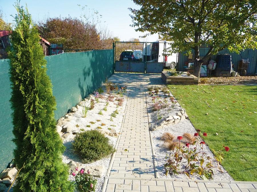 Klasický funkčný chodníkový obrubník sa dá efektívne zamaskovať výsadbou, podobnými materiálmi ako je kameň a drobný riečny štrk.