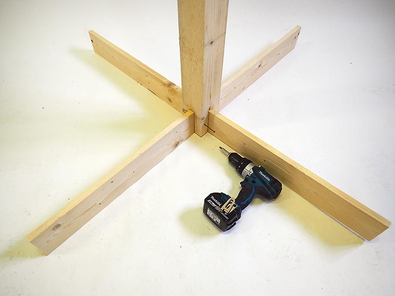 Kríž z dosiek vlepíme do vydlabaných drážok v stredovom hranole a spevníme ho skrutkami ø 5 × 80 mm zo štyroch strán.
