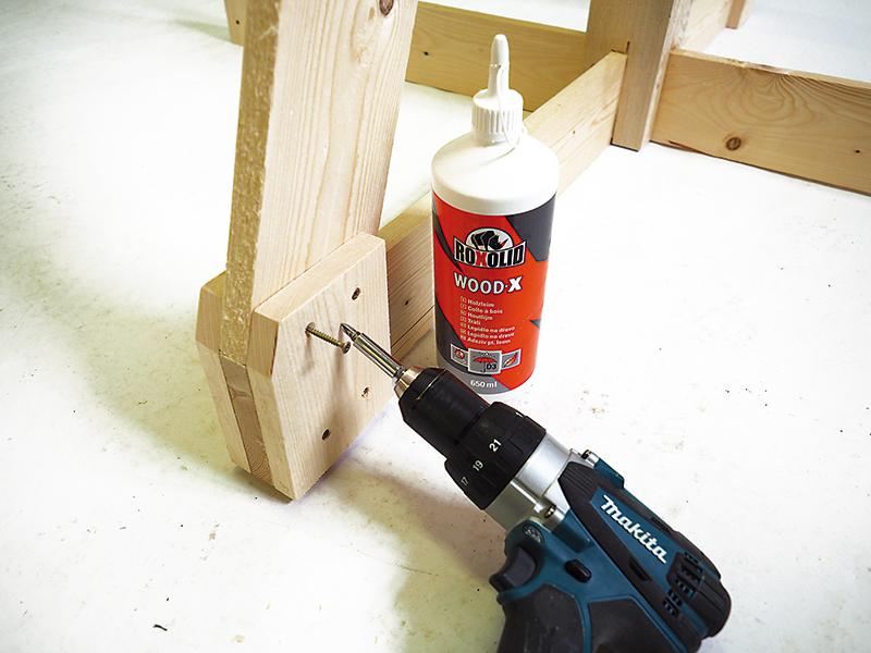 Upevníme spodnú časť nosníka. Nanesieme lepidlo, vložíme nárožný nosník a priskrutkujte ho skrutkami s priemerom 4 × 50 mm.