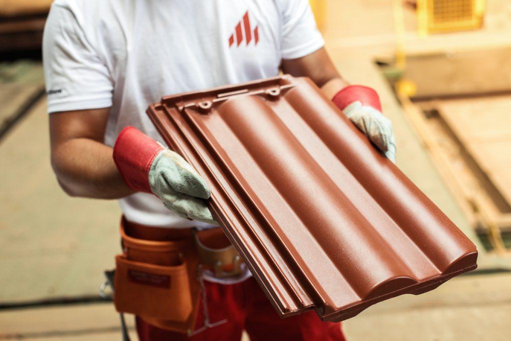 Škridla v rukách stavbára