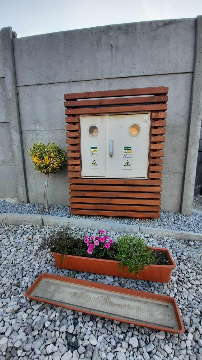 rozvodná skriňa v drevenom ráme s kvetináčom