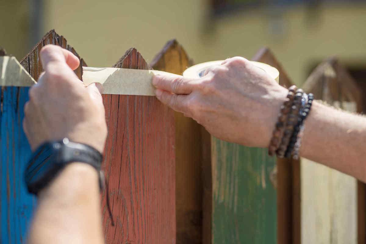Aplikácia pásky na plot pred maľovaním