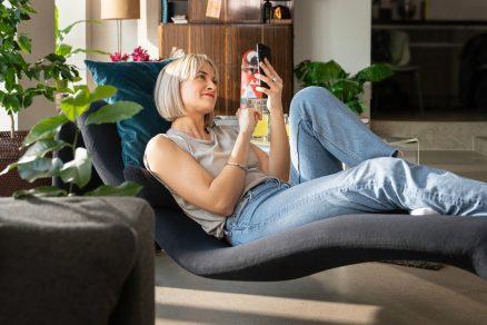 Žena leží na kresle a pozerá do mobilu