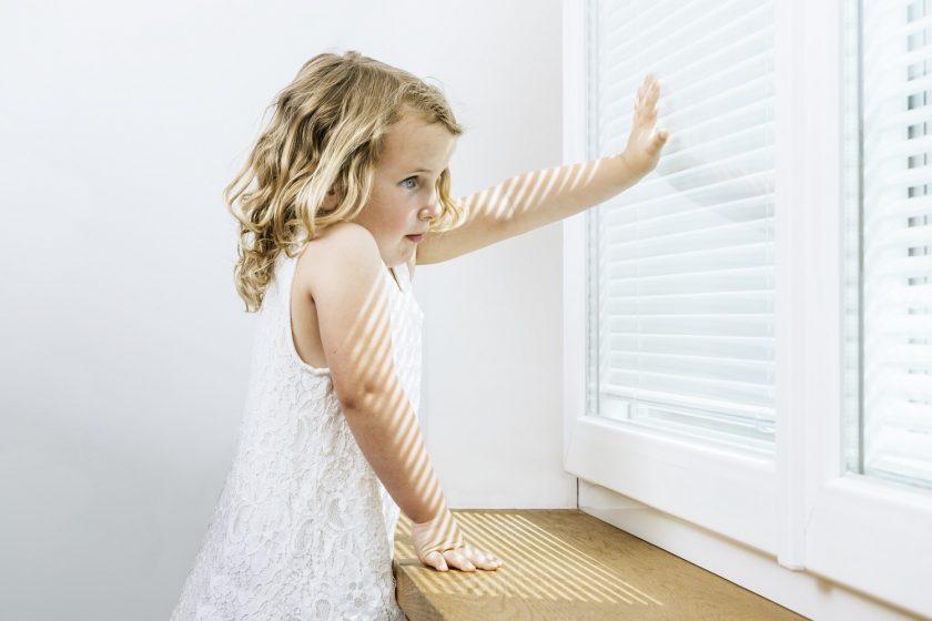 Dievčatko sa drží okna so žalúziou