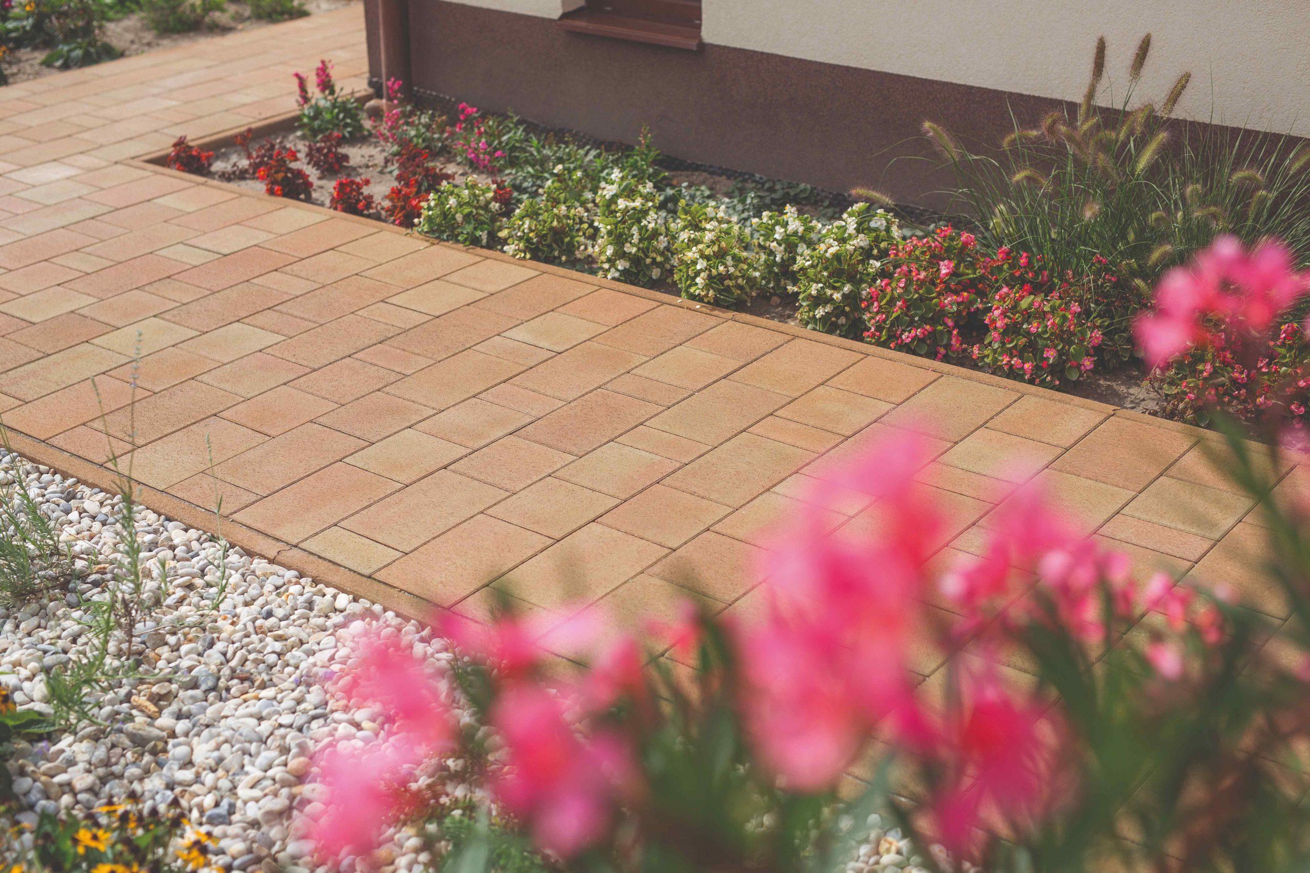 Dlažba tehlová na chodníčku pri dome s kvetinami