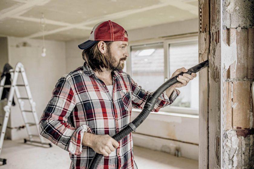 Muž vysáva stenu