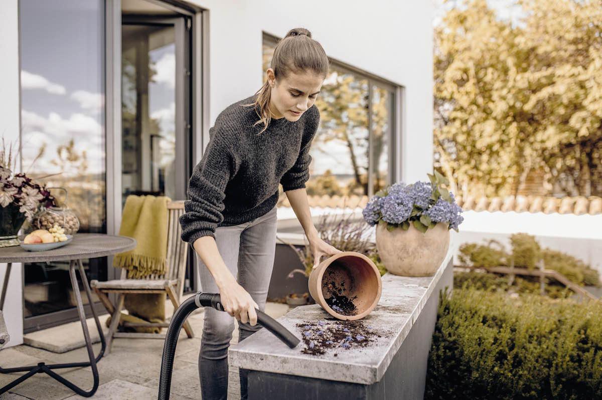 Žena sa vysáva v záhrade hlinu