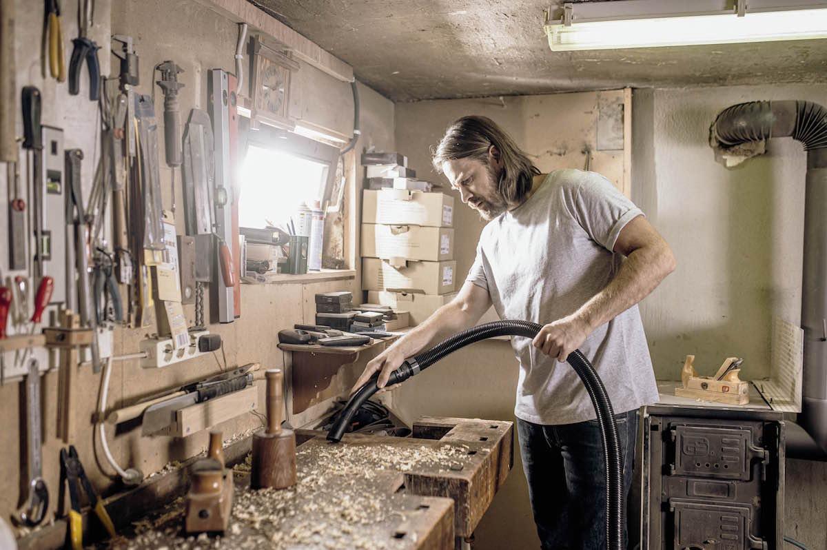 Muž vysáva v dielni