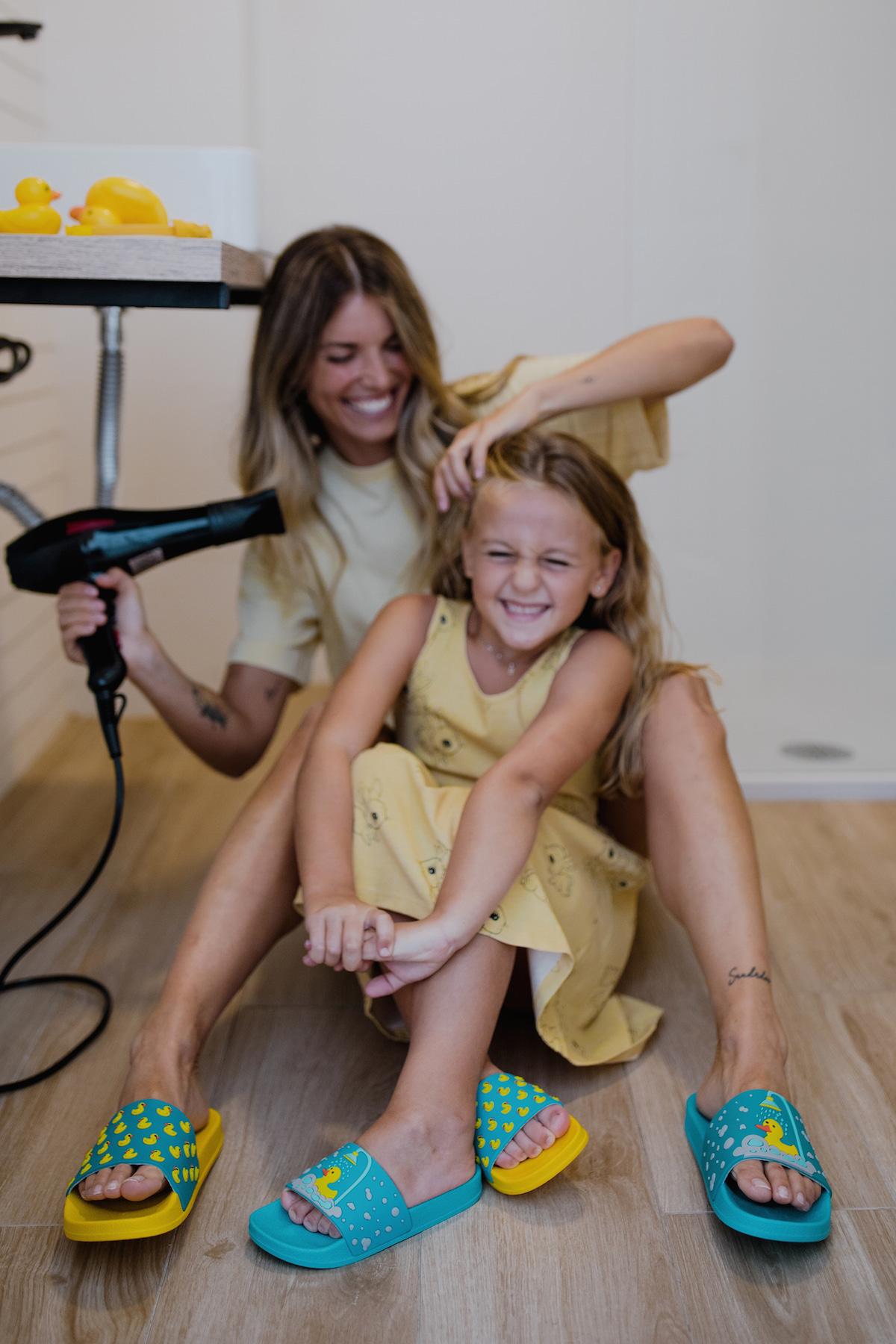 Žena fénuje vlasy dcére a smejú sa
