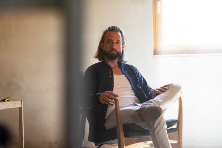Muž s dlhými vlasmi sediaci v kresle