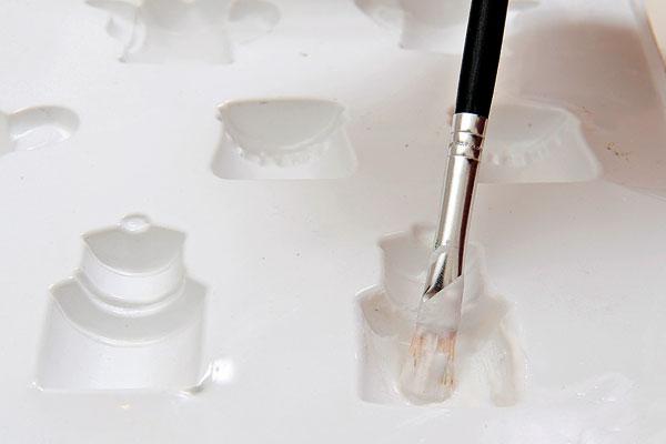 Štetcom naneste trocha hmoty na vnútornú stenu formičiek – zabránite tak tvorbe bubliniek.