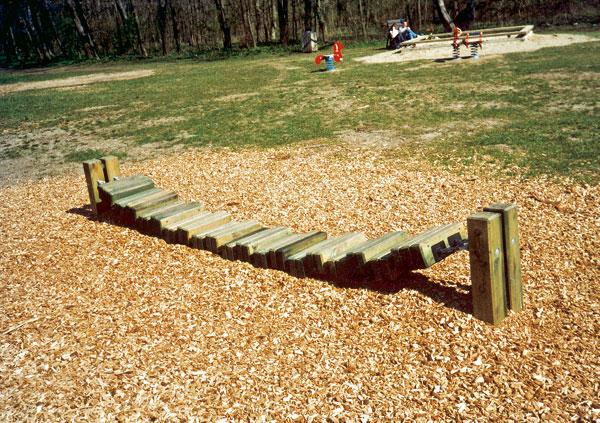 Prírodná hnedá farba drevenej štiepky v rôznych odtieňoch ladí s priznanou farbou dreveného detského visutého mostíka a okolitou zeleňou.